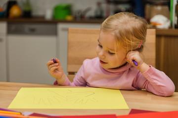 Kleines Mädchen malt zu Hause mit Buntstiften
