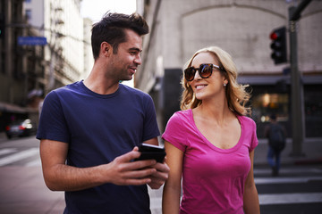 romantic couple with smartphone walking through los angeles