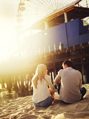 romantic couple sitting on beach with creative lens flare