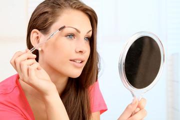 Frau korrekiert ihre Augenbrauen