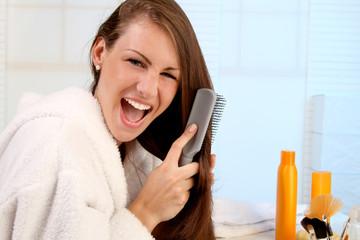 Junge Frau kämmt ihre widerspenstigen Haare
