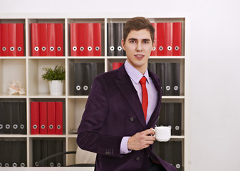 Man posing with coffee cup in office