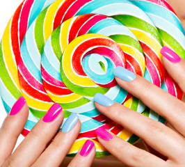 female fingers with colorful nails on the background of vivid mu