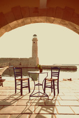 Old vintage cafe and lighthouse on the sea  Rethymnon Crete, imp