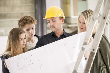 Engineer showing blueprint to family