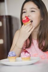 Happy girl eating cupcake