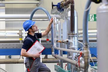 Monteur in einer Industrieanlage überprüft Anlage