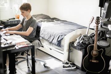 Teenage boy typing on laptop