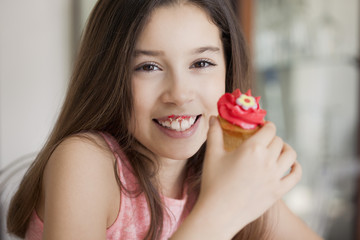 Happy girl eating cupcake