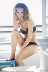 Beautiful woman sitting in bathroom and smiling