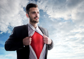 Businessman as superhero over sky background