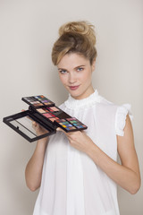 Beautiful woman holding eyeshadow palette