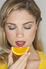 Close-up of a woman eating a slice of orange