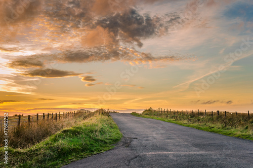 Leinwanddruck Bild Sunset over a Country Road