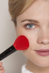 Portrait of a woman using make-up brush on her face
