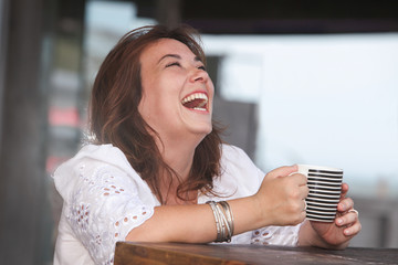laughing woman with a cup of dring