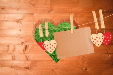 Composite image of hearts hanging on line with card