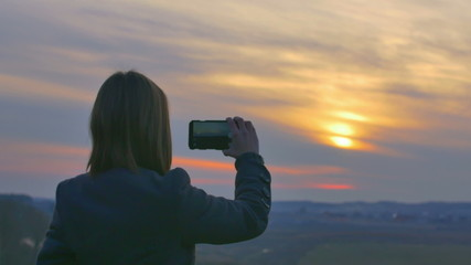 The young woman shot sunset with the phone. Slider camera move