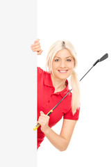 Female golfer posing behind a blank billboard
