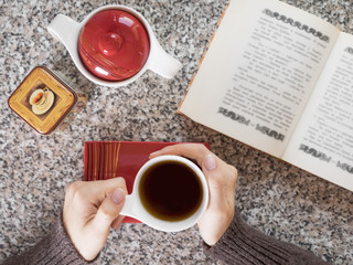 Girl drinking tea and reading a book