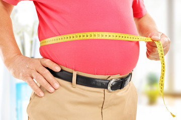 Close-up on a man measuring his belly
