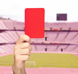Hand holding a red card in front of a stadium