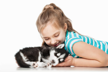 Girl with a puppy husky, on a gray background