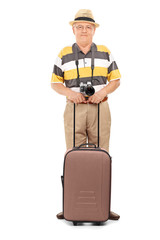 Mature tourist holding his luggage and posing