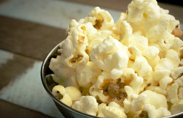 Cropped Popcorn in a silver bowl over wood background