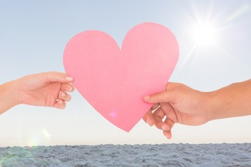 Composite image of couple passing a paper heart