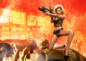 Sexy blonde woman with rifle in fire