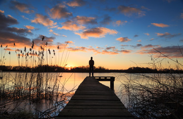 Man standing on a jetty during a winter sunset over a lake.