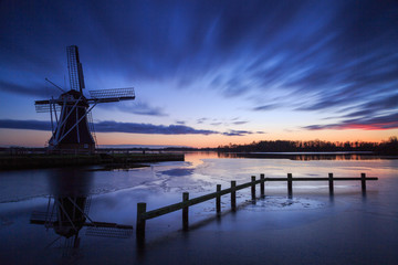 Traditional windmill at a lake during a cold sunset in winter.