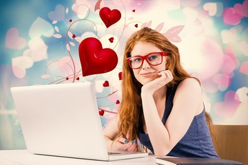 Composite image of pretty redhead working on laptop
