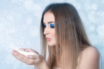 Girl with bright blue make-up blowing on snow