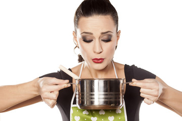 young housewife blow to the pot with food