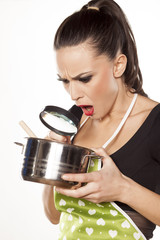 woman looking with a magnifying glass in a pan with food