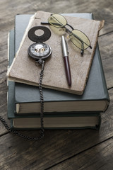 An antique pocket watch, glasses and books
