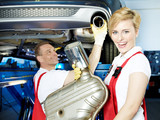 Car mechanics fixing the exhaust system of a car