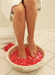 Fussbad mit roten Rosenblaettern