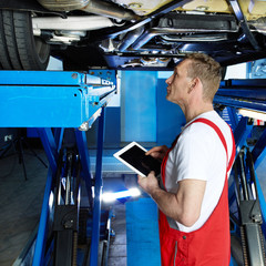 Mechanic inspecting the engine of a car with tablet