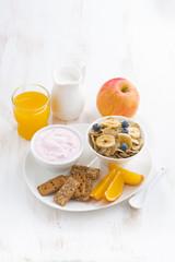 healthy breakfast - cereal, fruit, yogurt and juice, vertical