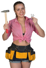 Woman in tool belt holding hammer and nails
