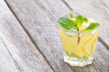 refreshing mint lemonade in glass on a wooden background