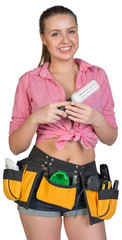 Woman in tool belt holding energy-saving lamp