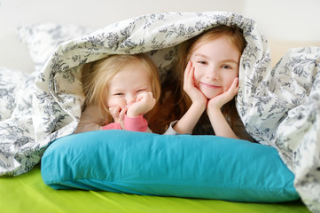 Two little sisters playing in bed