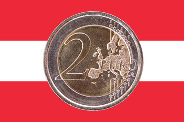 Common face of two euro coin on flag of Austria
