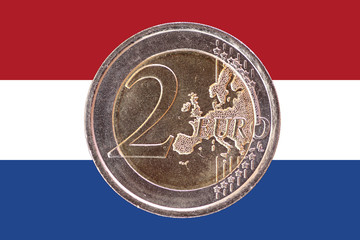 Common face of two euro coin on flag of Netherlands