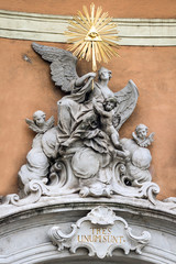Golden Baroque statue on the wall of a historic building in Brat