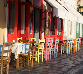 Greek island restaurants with colorful tables and chairs. © seqoya
